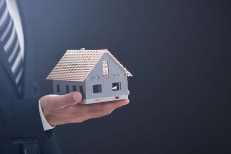 holding a model house suggesting house acquisition or rental