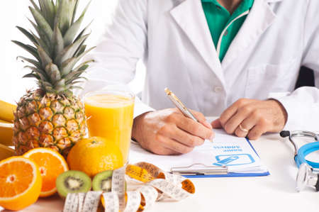 Nutrionist writing a diet plan on table with healthy fruits close up