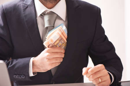 Businessman in suit with euro banknotes close up