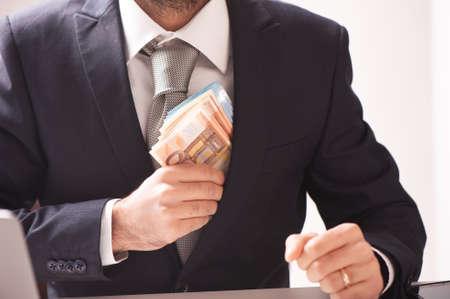 Geschäftsmann im Anzug mit Euro-Banknoten hautnah