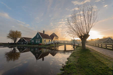 Traditional green dutch house with little wooden bridge against blue sky in the Zaanse Schans village. Holland Netherlands