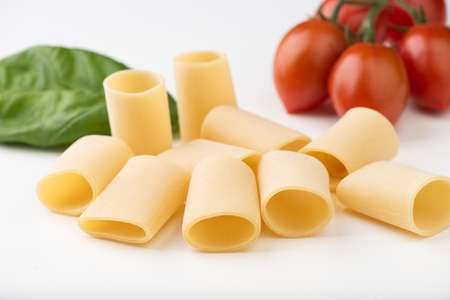 Raw pasta with basil and tomato on white surface close up