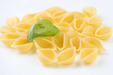 Raw pasta on white surface close up