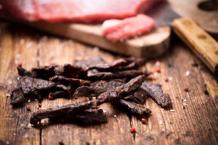 Beef Jerky on  wooden background close up Reklamní fotografie