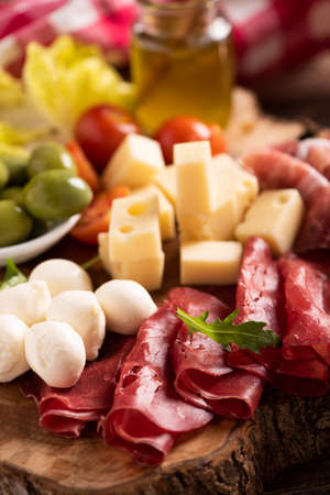 Antipasto catering platter with olives , jerky, salami and cheese close up