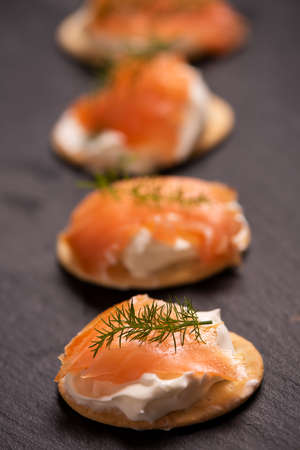 Canapes with salmon isolated on black close up
