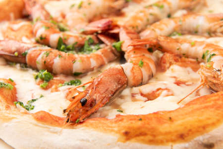 Whole seafood pizza with big shrimps close up