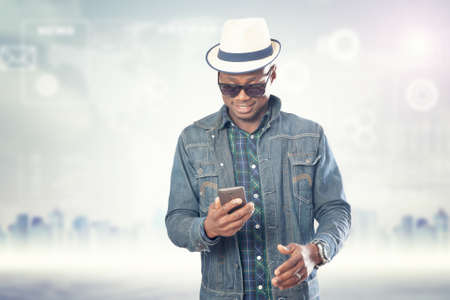 Young american african guy with cell phone. Handsome man. Device connecting people concept