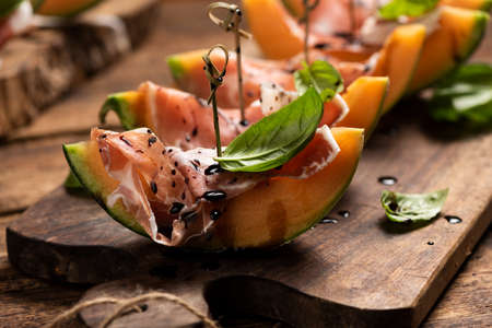 Sliced melon with ham and basil leaves, served on a wood chopping board close up Imagens - 122913628
