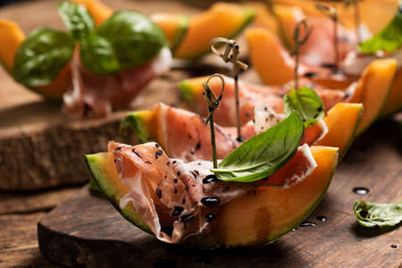 Sliced melon with ham and basil leaves, served on a wood chopping board close up Imagens - 122913634