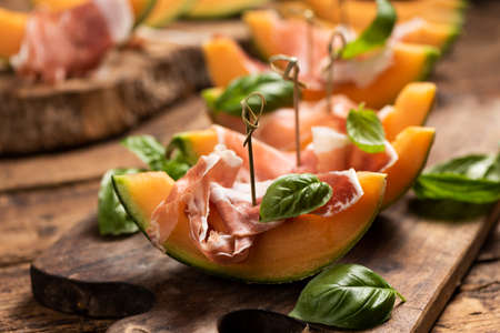Sliced melon with ham and basil leaves, served on a wood chopping board close up