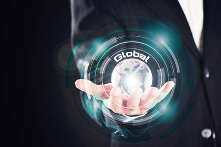 Hand holding translucent globe with word Global