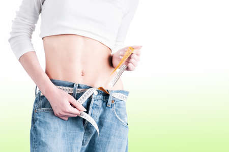 Girl with a tape measure used as belt to tighten jeans around waist on a green back goround. Dieting concept