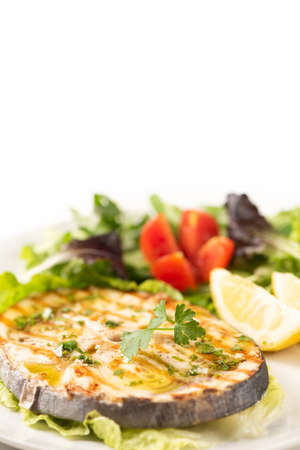 Grilled swordfish with salad and lemon on the white plate. Close up
