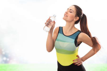 Beautiful young sports lady drinking water and  posing isolated over white