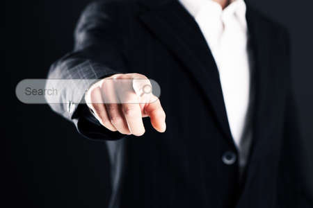 Business man pointing finger on a bar search on dark