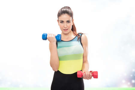Happy fitness girl practicing sports doing weights with dumbbells on white