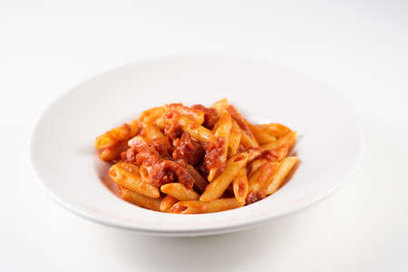 Italian Amatriciana Pasta with tomato sauce and smoked bacon served on white plate