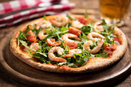 Pizza covered with roquette and shrimps on wooden table close up