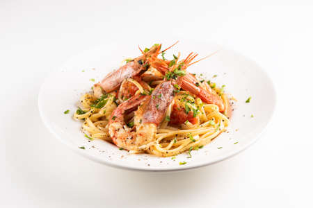 Linguine with garlic and king prawns on a plate on white Stockfoto