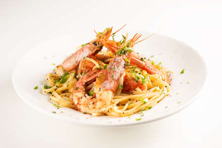 Linguine with garlic and king prawns on a plate on white 版權商用圖片