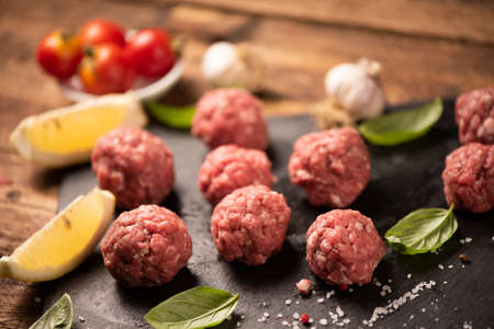 Raw meatballs on the cutting  black board close up