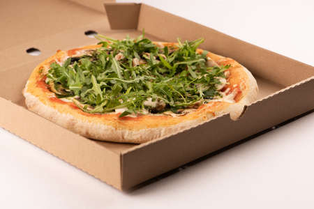 Fresh delivered pizza wiith rucola in cardboard box close up