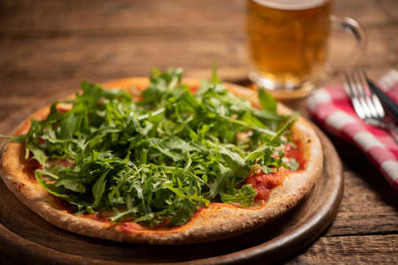 Italian Pizza with tomatoes, mozzarella cheese and arugula on wooden cutting board close up
