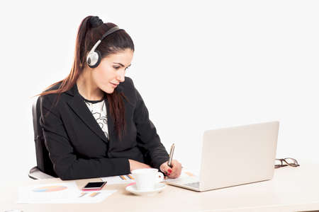 Attractive businesswoman is wearing a headset and looking at the laptop from her desk on white