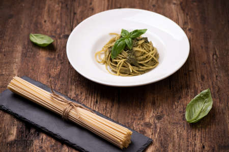 Spaghetti Pesto alla Genovese on rustic wooden table close up 版權商用圖片
