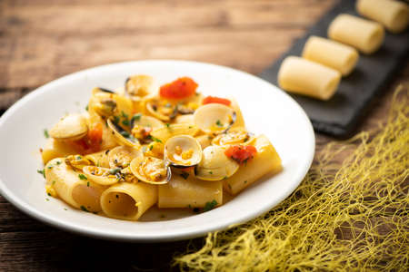 Paccheri pasta with clams on white plate on rustic wooden table 版權商用圖片