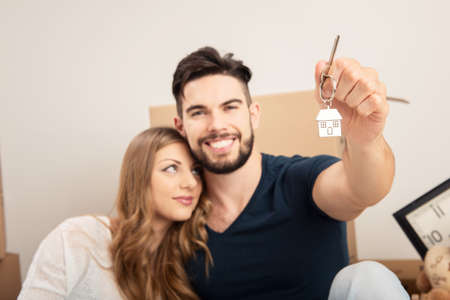 Young smiling couple holding their new house keys, real estate and relocation concept close up
