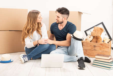 Moving Home. Couple sitting on the floor in a new house close up Banque d'images - 137188610