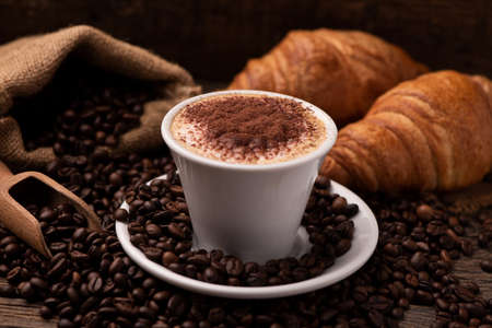 Cappuccino and croissant with coffee beans close up