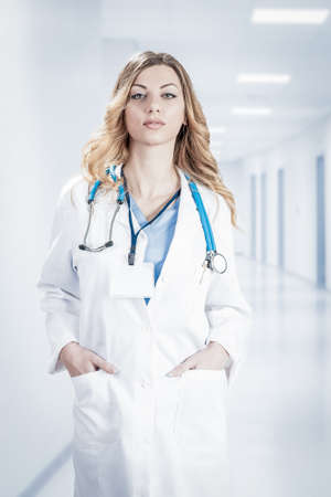Female doctor in white surgical coat with stethoscope and blue paper holder in hands standing isolated on white background