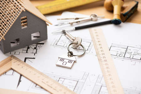 Ein Musterhaus auf Blaupausen mit Schlüsseln zum neuen Zuhause. Nahaufnahme Standard-Bild