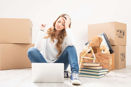 A Blonde young woman renovating her home sitting on the floor surrounded by cardboard packing cartons using a tablet-pc