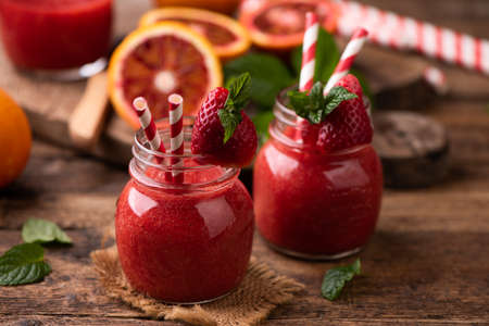 Strawberry smoothie in glass jar, over old wood table. close up Banque d'images - 142153141