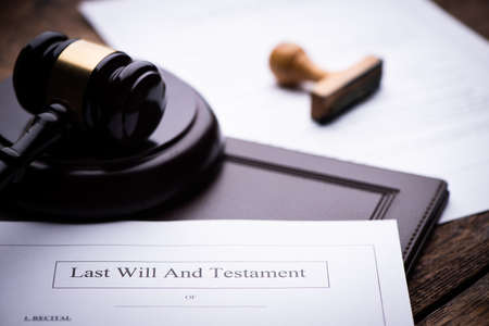 Last Will and testament document on wooden table close up