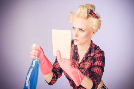 Blonde pin up woman in gloves holding spray bottle for cleaning concept or sanitizing