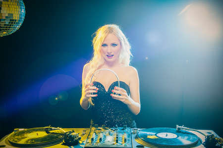 A beautiful blonde DJ girl in a white suit on decks on the party on the black background