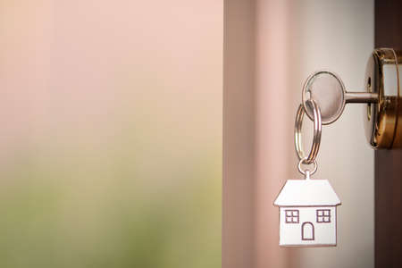 House key on a house shaped silver keyring in the lock of a entrance brown door with copy space Banque d'images