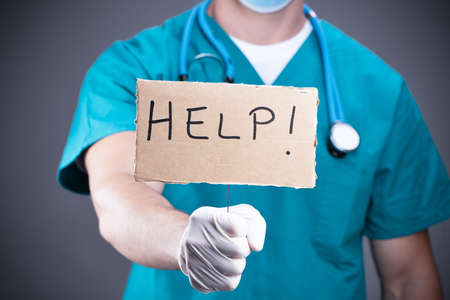 A Closeup portrait of health care professional with red tie and stethoscope holding up a sign which says Help