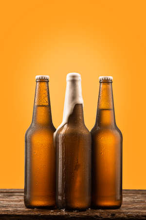 Cold bottle of beer on wood and yellow background close up Foto de archivo