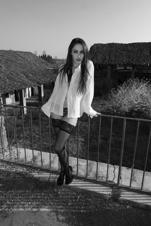 A stunning model posing in abandoned farmstead with black stockings and lingerie