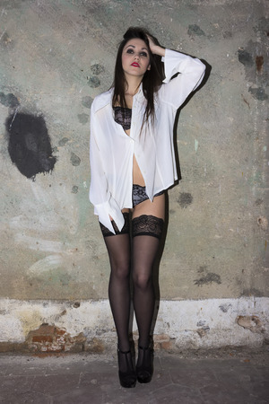 A stunning model posing in abandoned farmstead with black stockings and lingerie photo