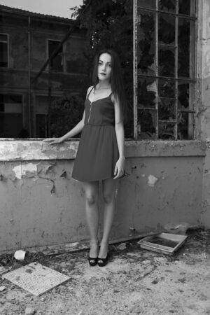 Stunning young model posing in a red dress, in abandoned place