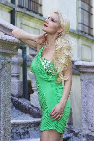 Fantastic and classy model posing in short green dress