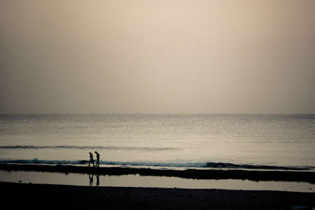 Las Americas Spain, December 09 2014: two people walking togheter near the ocean in the sunset. photo
