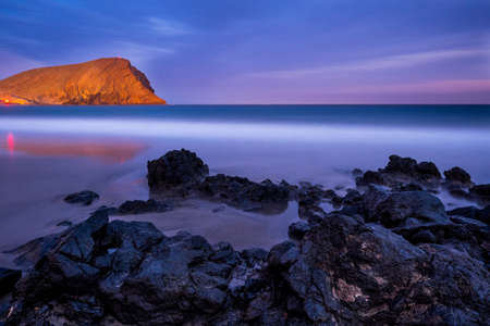 Montana Roja by night with rocks and ocean Stock Photo